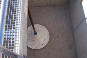 Foto van bovenaf. Hyperboloïde menger geïnstalleerd in een rechthoekige tank.
